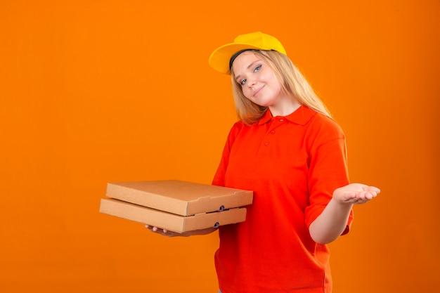 赤いポロシャツと分離のオレンジ色の背景に混乱して肩をすくめてピザの箱を保持している黄色の帽子を着ている若い配達の女性 無料写真