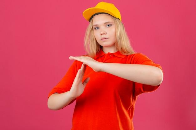 Молодая курьерская женщина в красной рубашке поло и желтой кепке выглядит перегруженной, делая жест тайм-аута руками на изолированном розовом фоне Бесплатные Фотографии