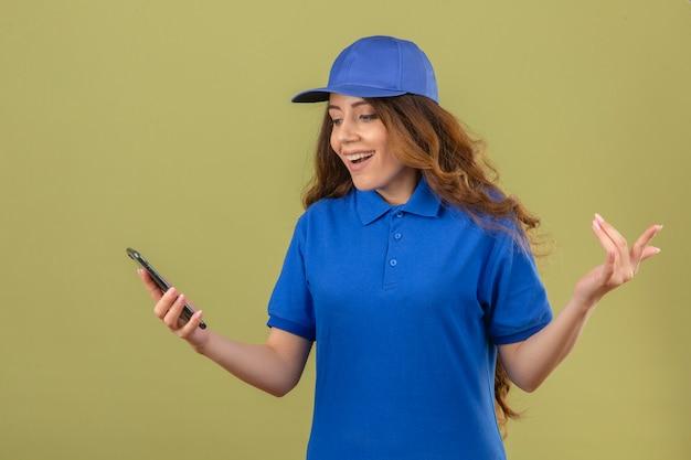 Giovane donna delle consegne con capelli ricci che indossa la maglietta polo blu e cappuccio guardando lo schermo dello smartphone sorpreso sorridente con la faccia felice con la mano alzata su sfondo verde isolato Foto Gratuite