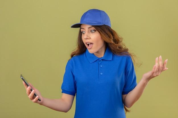 Giovane donna delle consegne con i capelli ricci che indossa la maglietta polo blu e cappuccio guardando lo schermo dello smartphone sorpreso con la mano sollevata su sfondo verde isolato Foto Gratuite