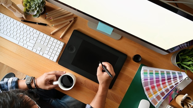 Young designer drawing sketches on digital graphic tablet at studio. top view shot Premium Photo