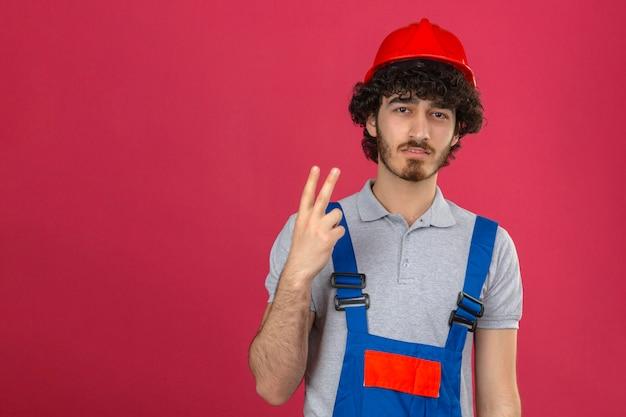 Молодой недовольный панированный красивый рабочий-строитель в строительной форме и защитном шлеме показывает пальцами номер два на изолированном розовом фоне и указывает вверх Бесплатные Фотографии