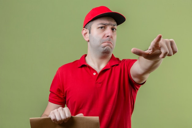 고립 된 녹색 배경 위에 손가락으로 카메라를 가리키는 종이 패키지를 들고 빨간색 유니폼을 입고 젊은 불쾌 배달 남자 무료 사진