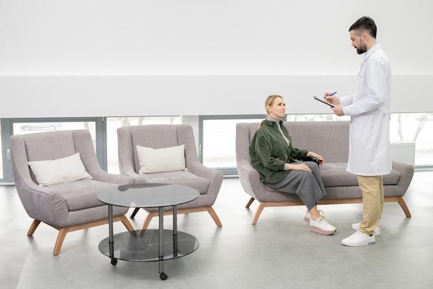 Молодой врач в белом халате делает заметки, стоя рядом с пациентом на диване в гостиной современной клиники Premium Фотографии