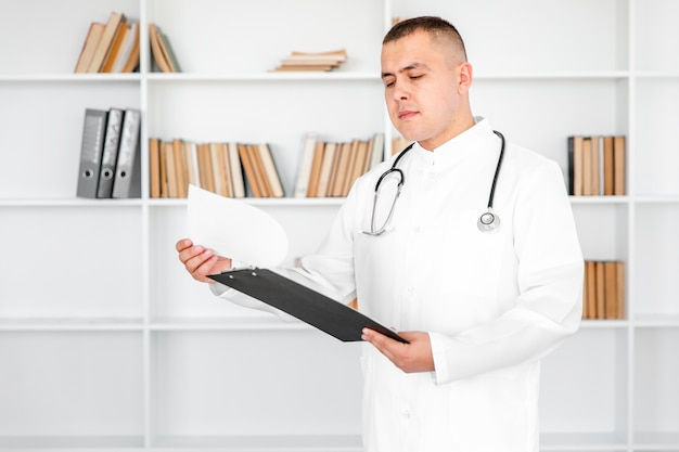 Young doctor looking on sheets from a clipboard Free Photo