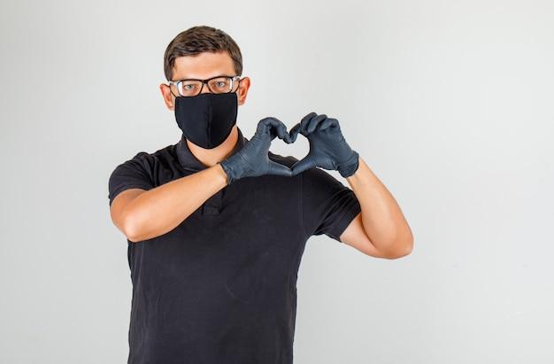 若い医者が黒いポロシャツで心のジェスチャーを作ると喜んで 無料写真