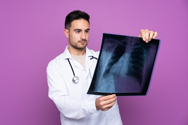 Young doctor man over isolated wall Premium Photo