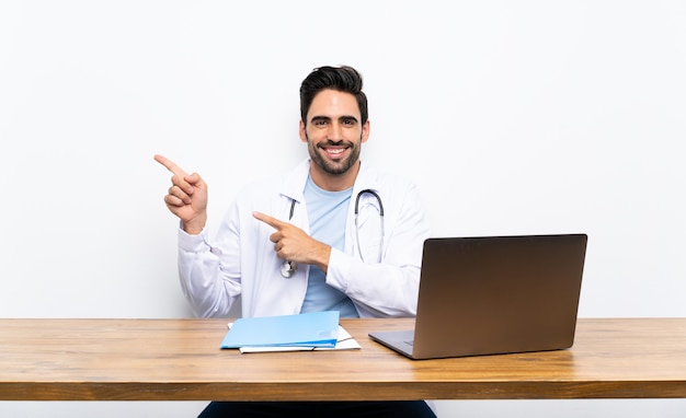 Young doctor man with his laptop over isolated wall pointing finger to the side Premium Photo