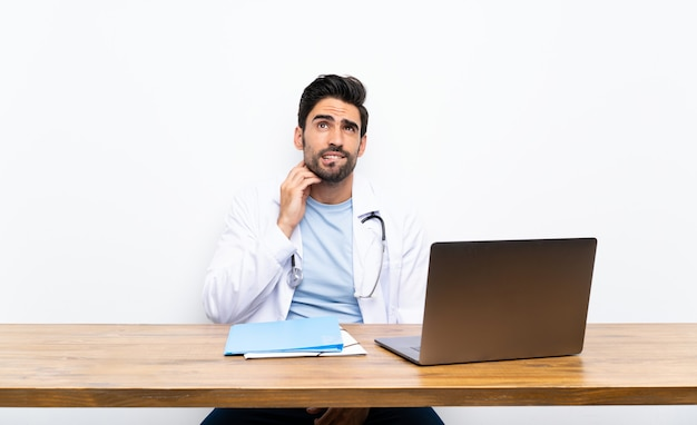 Young doctor man with his laptop over isolated wall thinking an idea Premium Photo