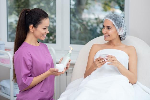 Молодой врач, рекомендующий косметику женщине Premium Фотографии