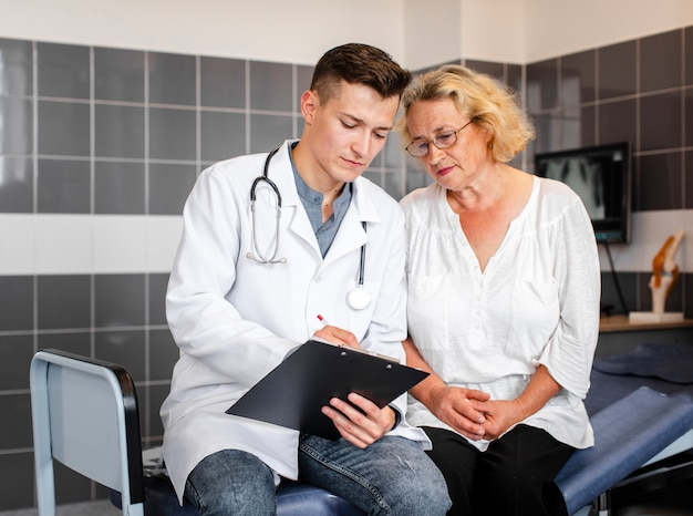 Young doctor showing results to senior woman Free Photo