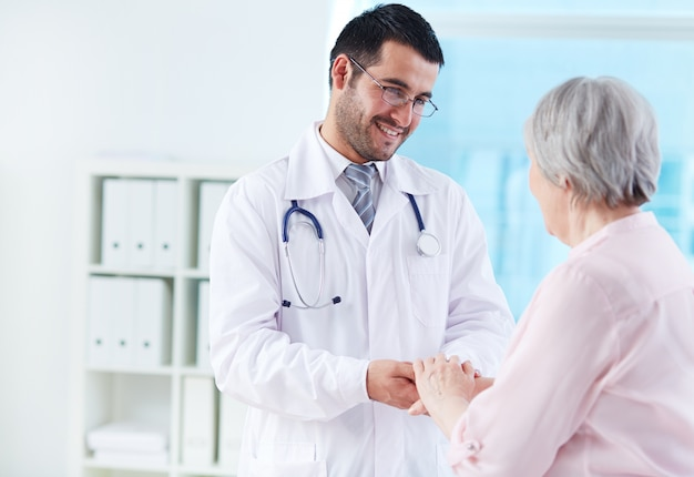 Young doctor supporting his patient Free Photo