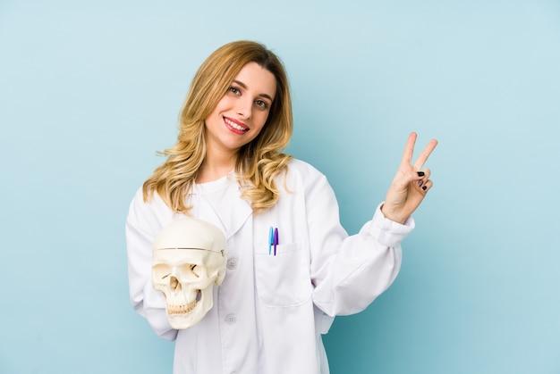 頭蓋骨を保持している若い医者女性は指で平和のシンボルを示すうれしそうな、のんきな分離しました。 Premium写真