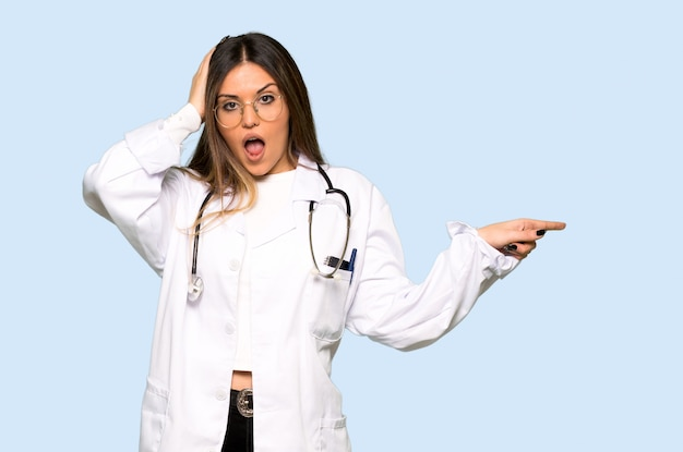 Young doctor woman pointing finger to the side and presenting a product on isolated blue background Premium Photo