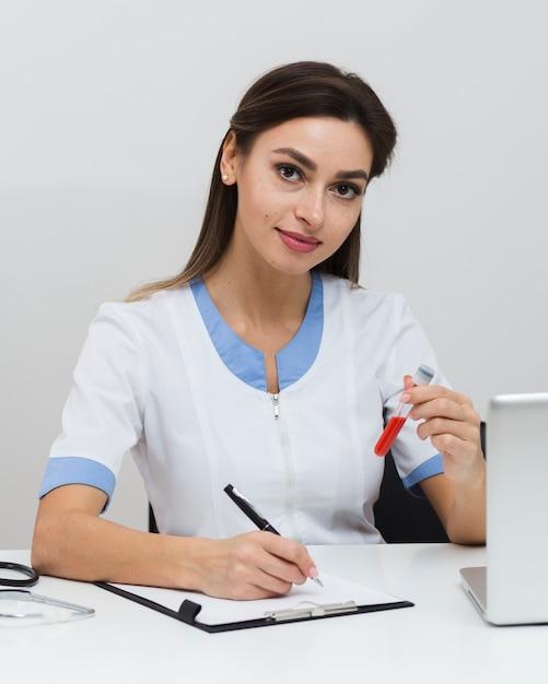 Giovane medico che scrive un rapporto e che tiene un campione di sangue Foto Gratuite