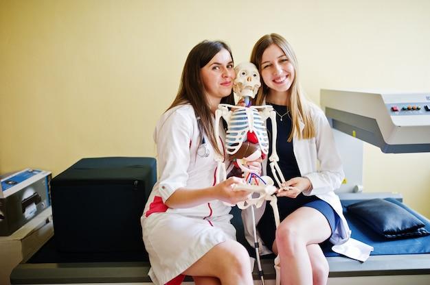 スケルトンでポーズをとって楽しんで若い医師。 Premium写真