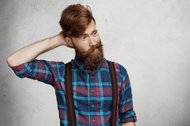 Young doubtful confused bearded man wearing checkered shirt and suspenders scratching his head in uncertainty, looking away with quizzical and questioning expression on his face, thinking of something Free Photo