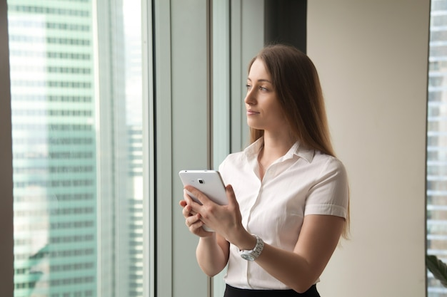 Young dreamy beautiful businesswoman looking through window while holding tablet Free Photo