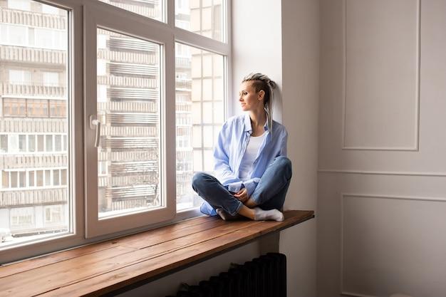 창에 앉아 험 상을 꿈꾸는 소녀 프리미엄 사진