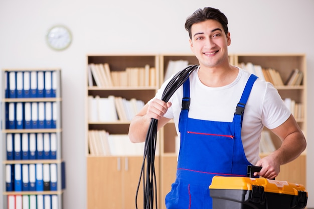 Young electrician with cable working in office Premium Photo