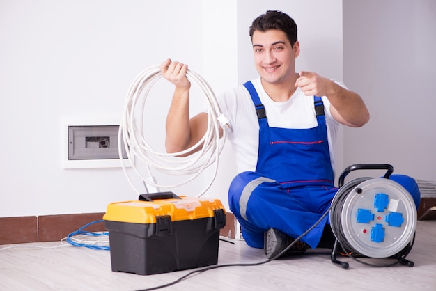 Young electrician working on socket at home Premium Photo