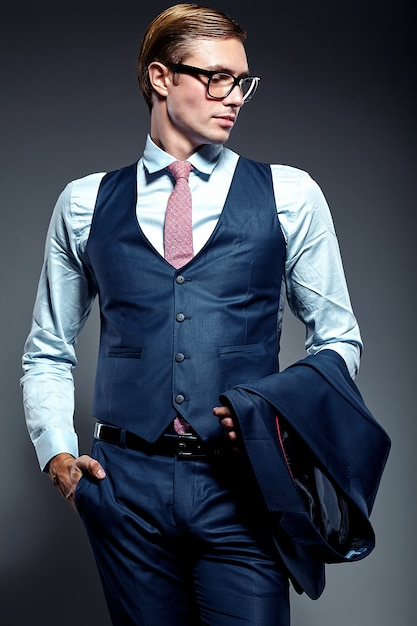 Young elegant handsome businessman male model in blue suit and fashionable glasses, posing in studio Free Photo