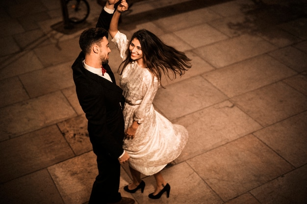 Young elegant man holding hand of whirling attractive cheerful woman Free Photo
