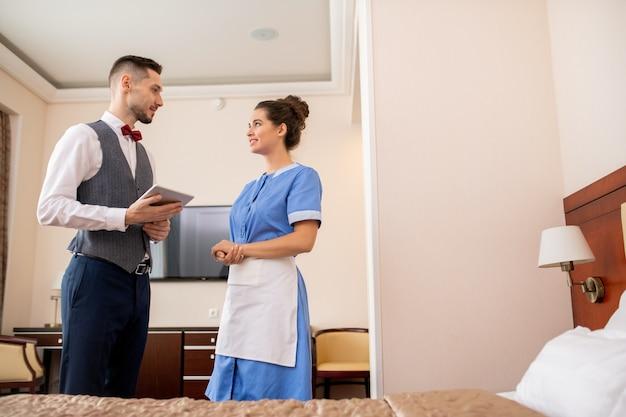 호텔 방에서 대화하는 동안 제복을 입은 예쁜 챔버 메이드를보고 터치 패드로 젊은 우아한 포터 프리미엄 사진