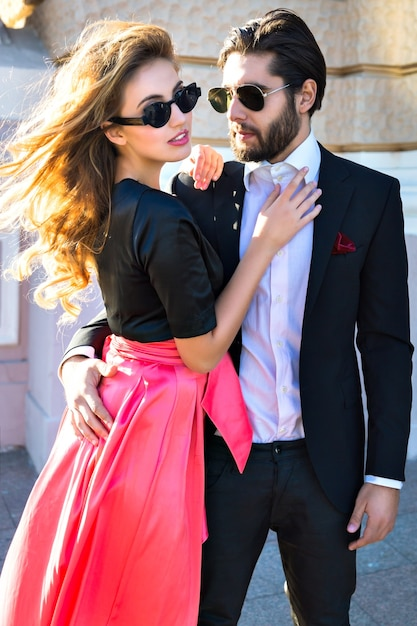 Young elegant sexy couple hugs on the street, wearing suit and glamour evening dress, enjoy their honeymoon vacation in europe, luxury style, love, stylish lovers Free Photo