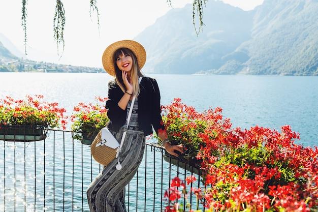 Молодая элегантная женщина в соломенной шляпе на балконе с цветами на озере комо Бесплатные Фотографии