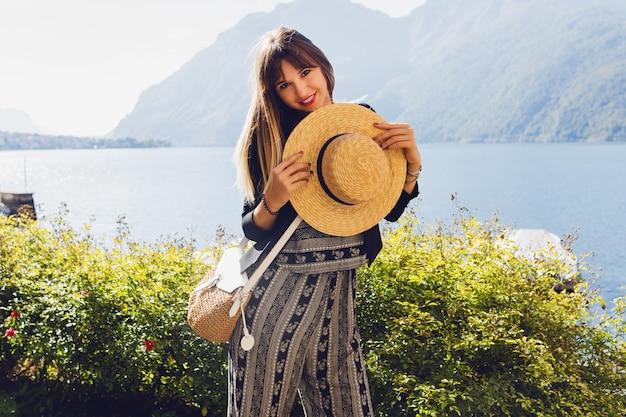 Молодая элегантная женщина в соломенной шляпе на озере комо Бесплатные Фотографии