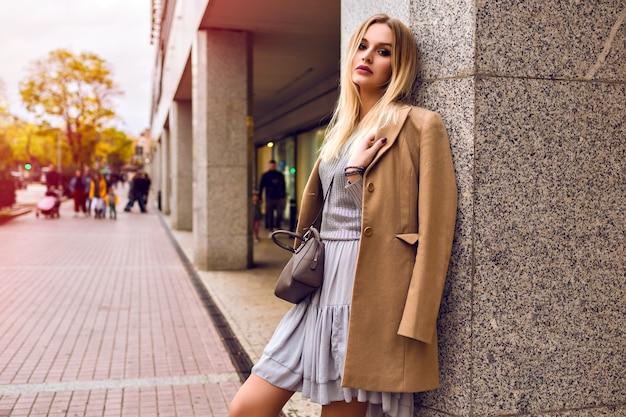 ショッピングセンターの近くの通りでポーズをとる若いエレガントな女性、魅力的な流行の衣装、ベージュのコート、銀のセーターとドレス、春、自然の美しさ 無料写真