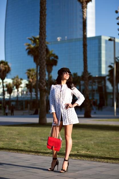 一人歩く若いエレガントな女性、トレンディなエレガントな服とアクセサリー、中年のセクシーな女性、トーンの色、手のひらの路地。 無料写真