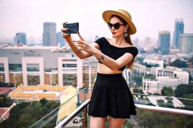 Giovane donna elegante che indossa abiti estivi alla moda alla moda che fanno selfie turistico sulla terrazza dell'hotel di lusso Foto Gratuite