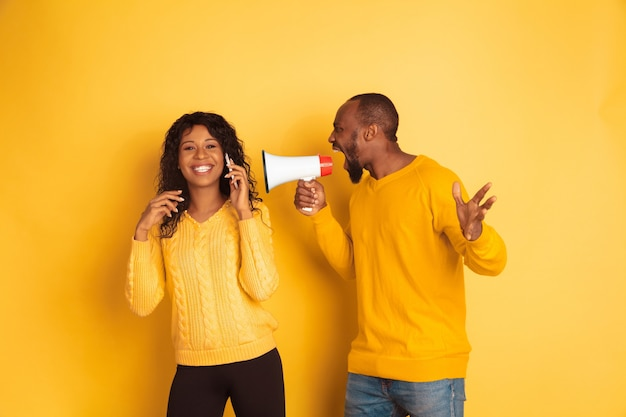Young emotional african-american man and woman in bright casual clothes on yellow space Free Photo