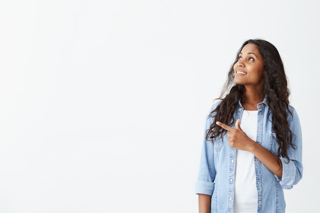 Young emotional african american woman in light-blue shirt with long black hair looking away, smiling showing teeth, pointing her finger at white wall with copy space Free Photo