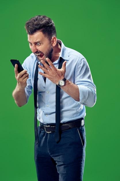 Il giovane uomo arrabbiato emotivo che grida su sfondo verde studio Foto Gratuite