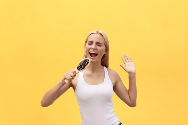 Young emotional woman singing with comb while dressing. isolated over yellow background. Premium Photo