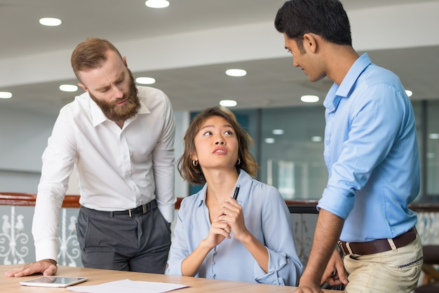 Young employee asking colleagues for help Free Photo