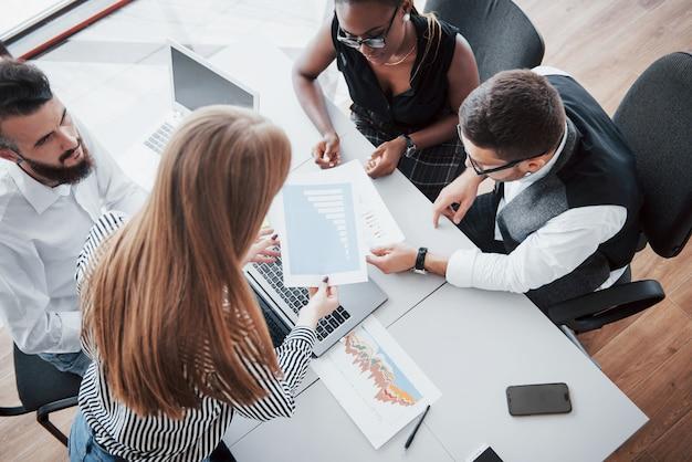 テーブルでオフィスに座っているとラップトップを使用して若い従業員は、チームのコンセプトはブレーンストーミング会議のコンセプトです。 無料写真