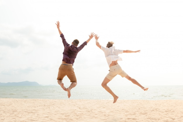Young energetic happy tourist men jumping at the beach Premium Photo