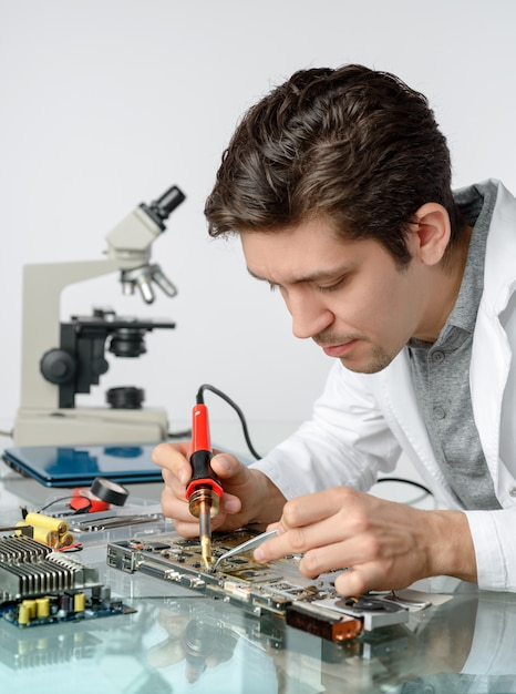 Young energetic male tech or engineer repairs electronics Premium Photo