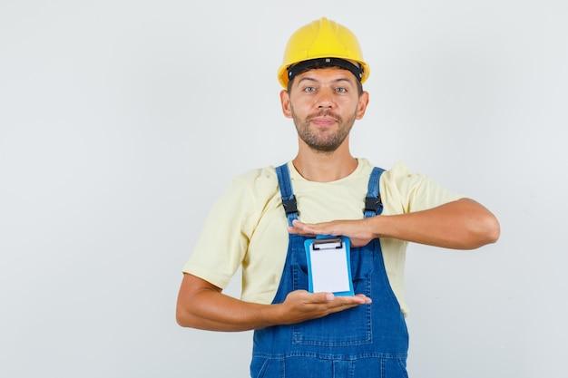젊은 엔지니어 유니폼에 미니 클립 보드를 들고 명랑, 전면보기를 찾고. 무료 사진