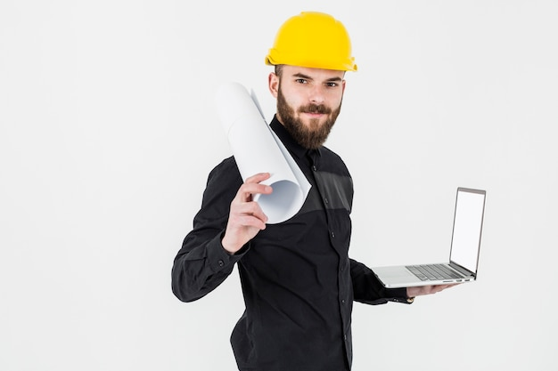 A young engineer holding rolledup blueprint and open laptop against white backdrop Free Photo