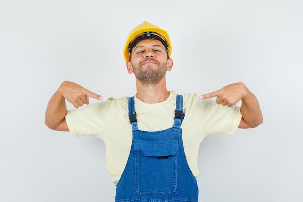 자신을 가리키고 자신감, 전면보기를 찾고 제복을 입은 젊은 엔지니어. 무료 사진