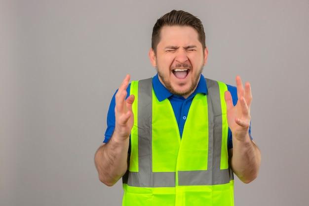 Giovane ingegnere uomo che indossa la costruzione giubbotto pazzo e pazzo gridando e urlando con espressione aggressiva e braccia alzate su sfondo bianco isolato Foto Gratuite