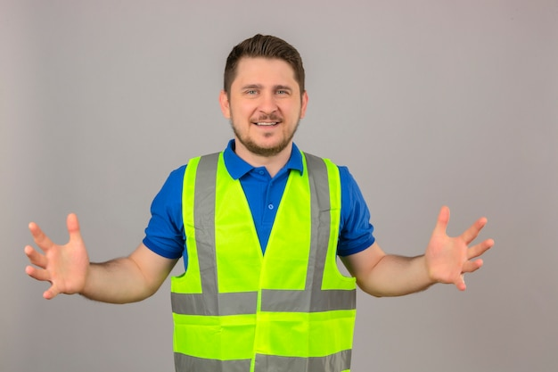 Молодой инженер человек, одетый в строительный жилет, жестикулирующий руками, показывающими символ меры знака большого и большого размера, улыбаясь, глядя в камеру на изолированном белом фоне Бесплатные Фотографии