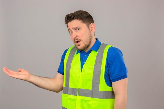 Giovane ingegnere uomo che indossa la maglia della costruzione cercando confuso in piedi con la mano sollevata avendo dubbi su sfondo bianco isolato Foto Gratuite