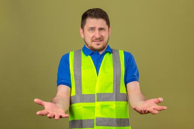 Giovane ingegnere uomo che indossa la maglia della costruzione cercando confuso in piedi con con le braccia e le mani sollevate su sfondo verde isolato Foto Gratuite