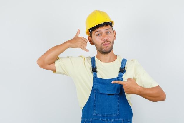 Молодой инженер показывает знак «позвони мне» в форме спереди. Бесплатные Фотографии